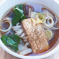 Noodle soup with shiitake mushrooms, udon noodles, Swiss chard, and fried gomasio tofu,