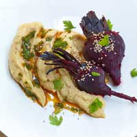 Beets cooked on a bed of salt with creamy orange chickpea puree,